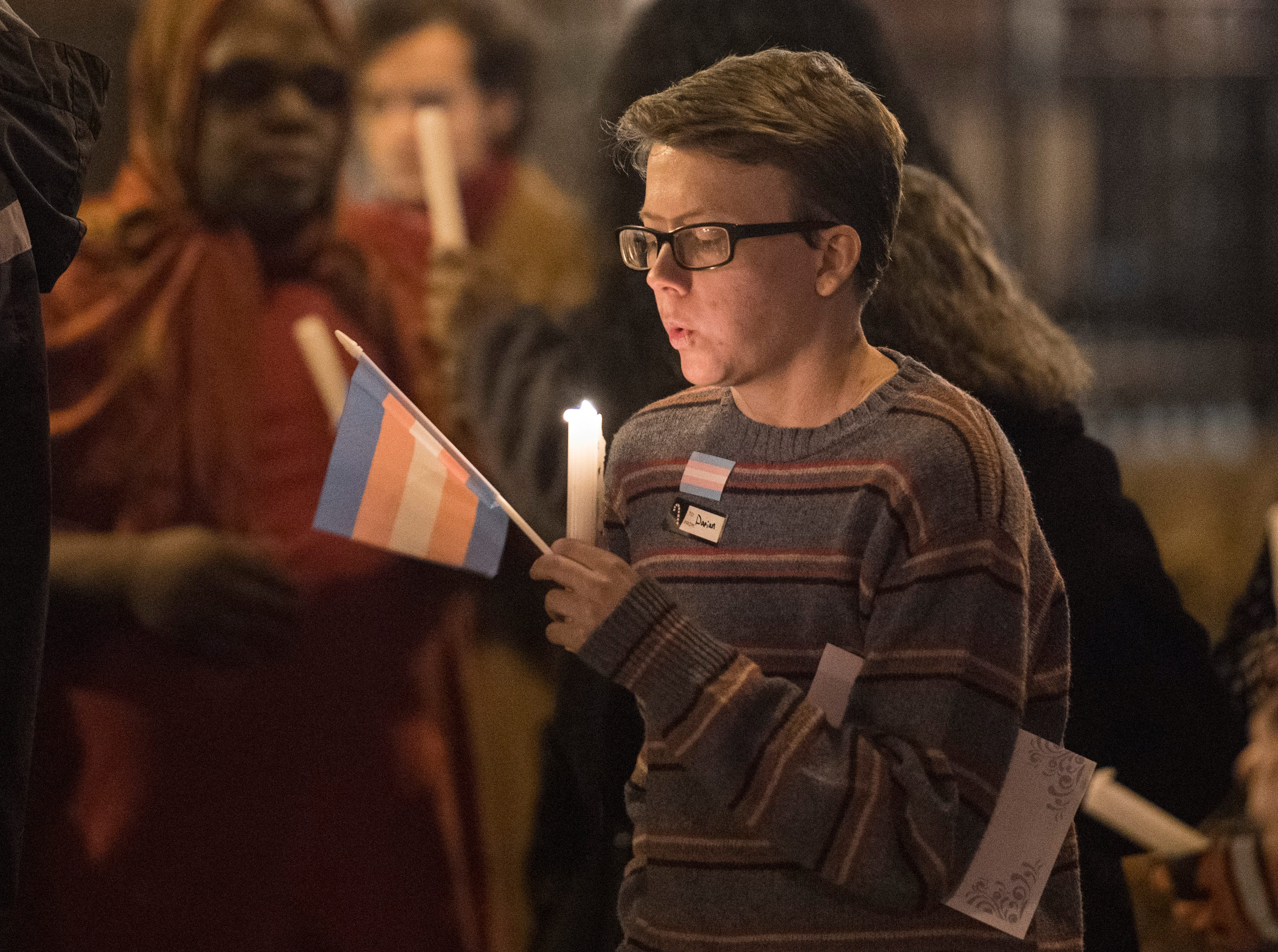 Darian Grigsby blows out a candle after a moment of silence during the candlelight vigil for Transgender day of Remembrance on Haynie's Corner Tuesday, Nov. 20, 2018.