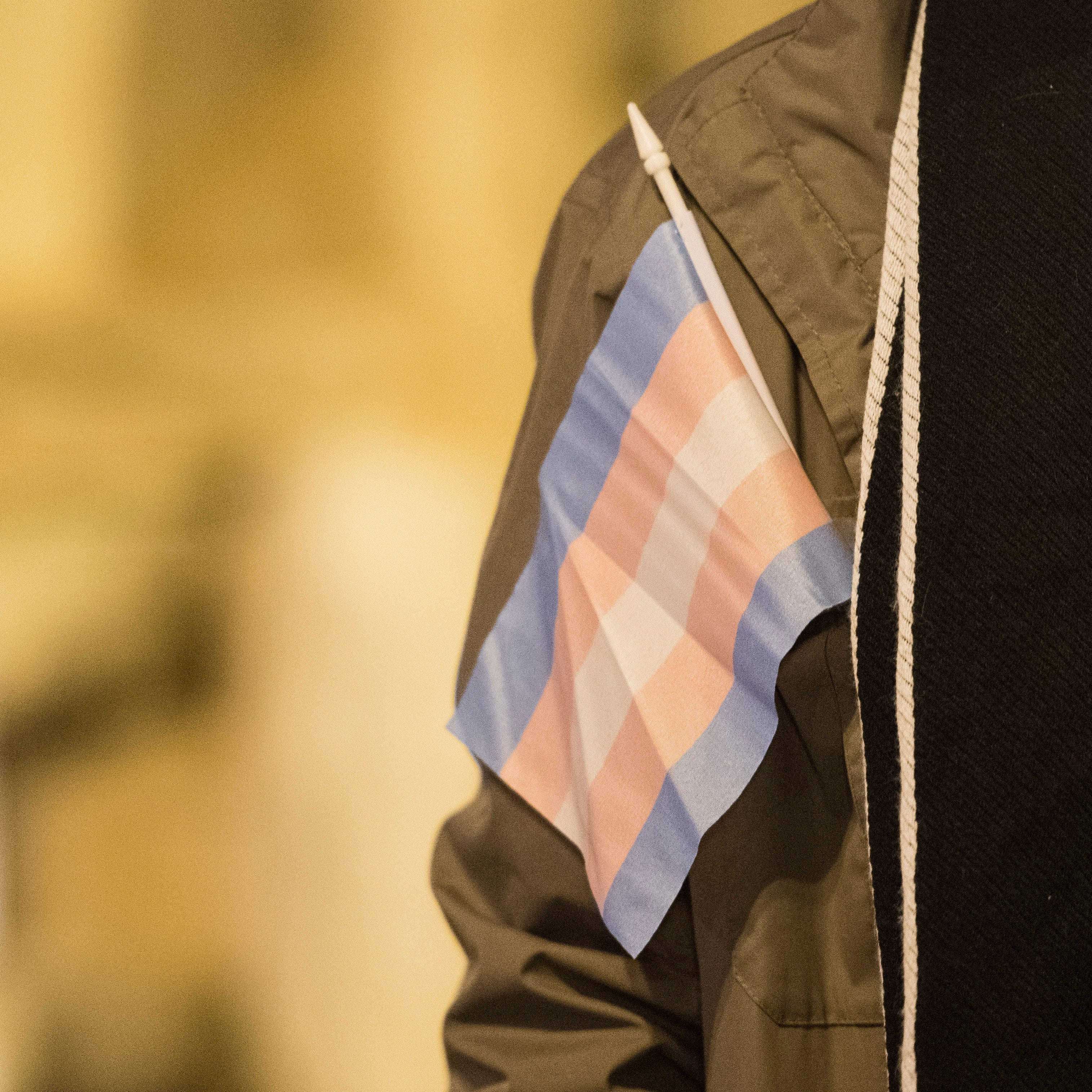 The transgender flag hangs out of a coat pocket during the candlelight vigil for Transgender day of Remembrance on Haynie's Corner Tuesday, Nov. 20, 2018.