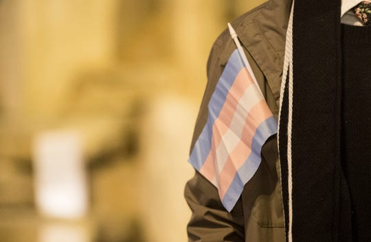 The transgender flag hangs out of a coat pocket during the candlelight vigil for Transgender Day of Remembrance on Haynie's Corner in Evansville, Indiana, on Tuesday, Nov. 20, 2018.