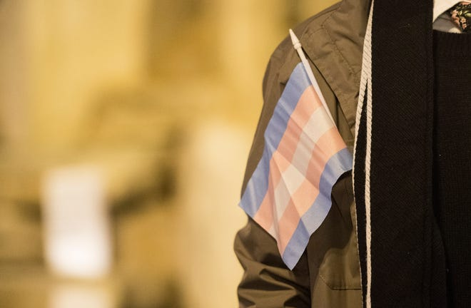 The transgender flag hangs out of a coat pocket during the candlelight vigil Nov. 20, 2018, for Transgender Day of Remembrance on Haynie's Corner in Evansville, Ind.