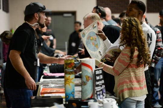 Attendees at the second annual Flat Earth International Conference examine some flat earth maps at the Crowne Plaza Denver Airport Convention Center in 2018. The idea of the earth being a flat disc has enjoyed a 21st century resurgence thanks to the internet.