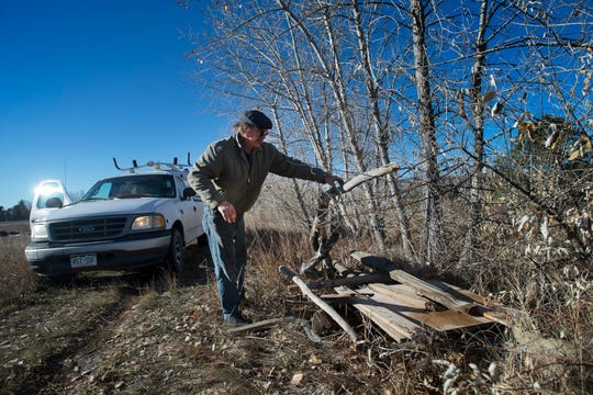 Pleasant Valley Lake and Canal Company ditch rider Ed Wendel clears a pile of scrap wood from the path along the East bank of the canal on Wednesday, Nov. 21, 2018, in Fort Collins, Colo.