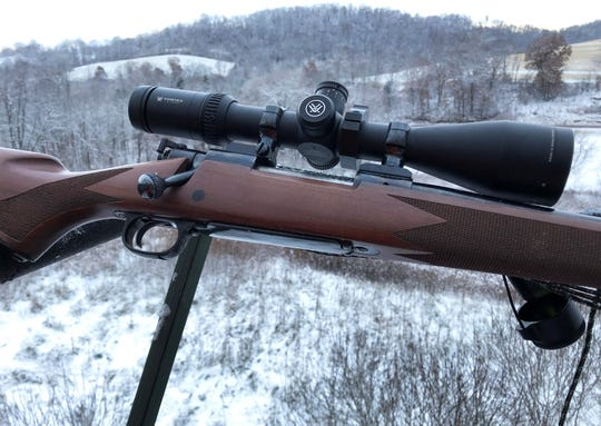 Patrick Durkin's deer rifle rests atop the railing of his tripod stand in Richland County on opening morning of Wisconsin's deer season.