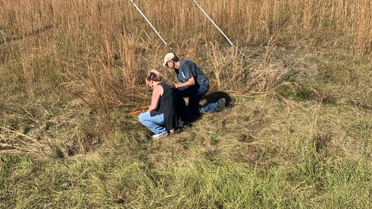 Cindy Dobson kneels Wednesday, Nov. 21, 2018, at the site where her son James Dobson, a cyclist, was killed Nov. 13 on U.S. 98 in Lamar County, Mississippi. She is comforted by Central Lamar Volunteer Fire Chief Reggie Ridgway.