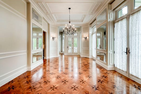 The hardwood floor in the dining room is patterned while the room is flanked with large mirrors. There's a door leading directly to the kitchen and an opening that leads to the breakfast nook.