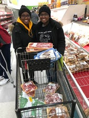 Sisters Ciatu and Ciana Fahnbulleh show their cart full of ingredients for their Liberian Thanksgiving meal Nov. 21 at Saraga International Grocery in Indianapolis.