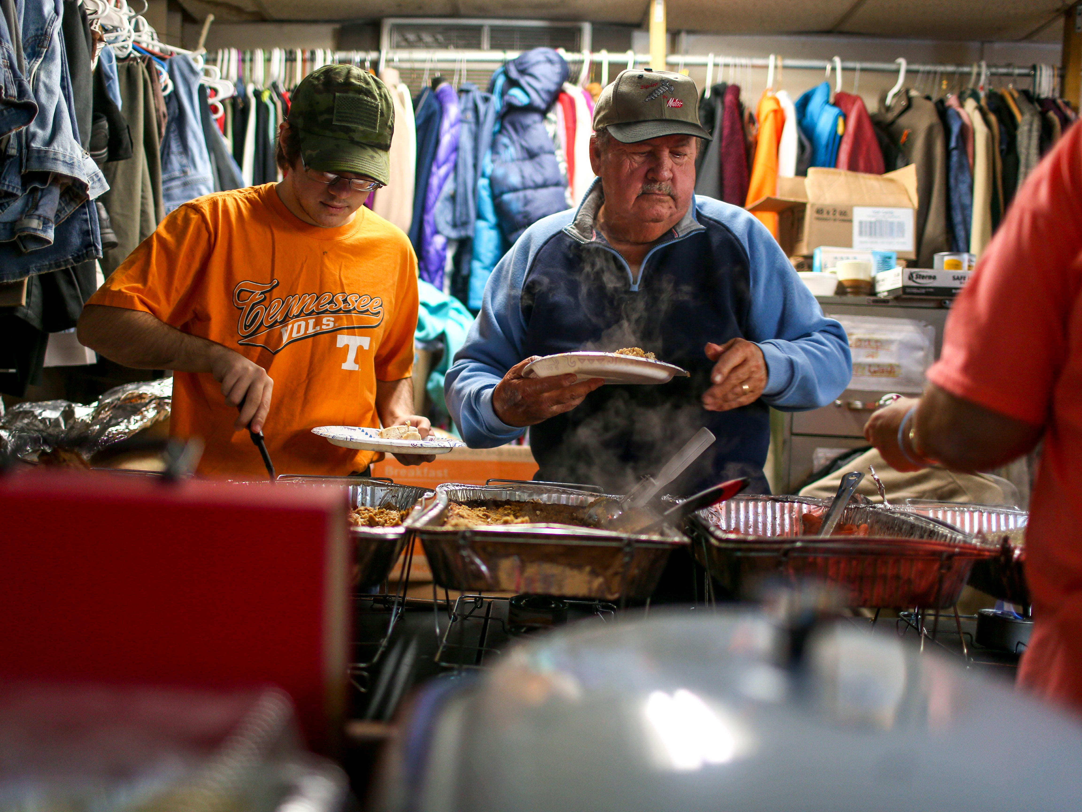 Gary Jack, right, prepares plates of food with other volunteers at the annual Thanksgiving meal put on by Safe Harbor Day Mission in Jackson, Tenn., on Wednesday, Nov. 21, 2018.