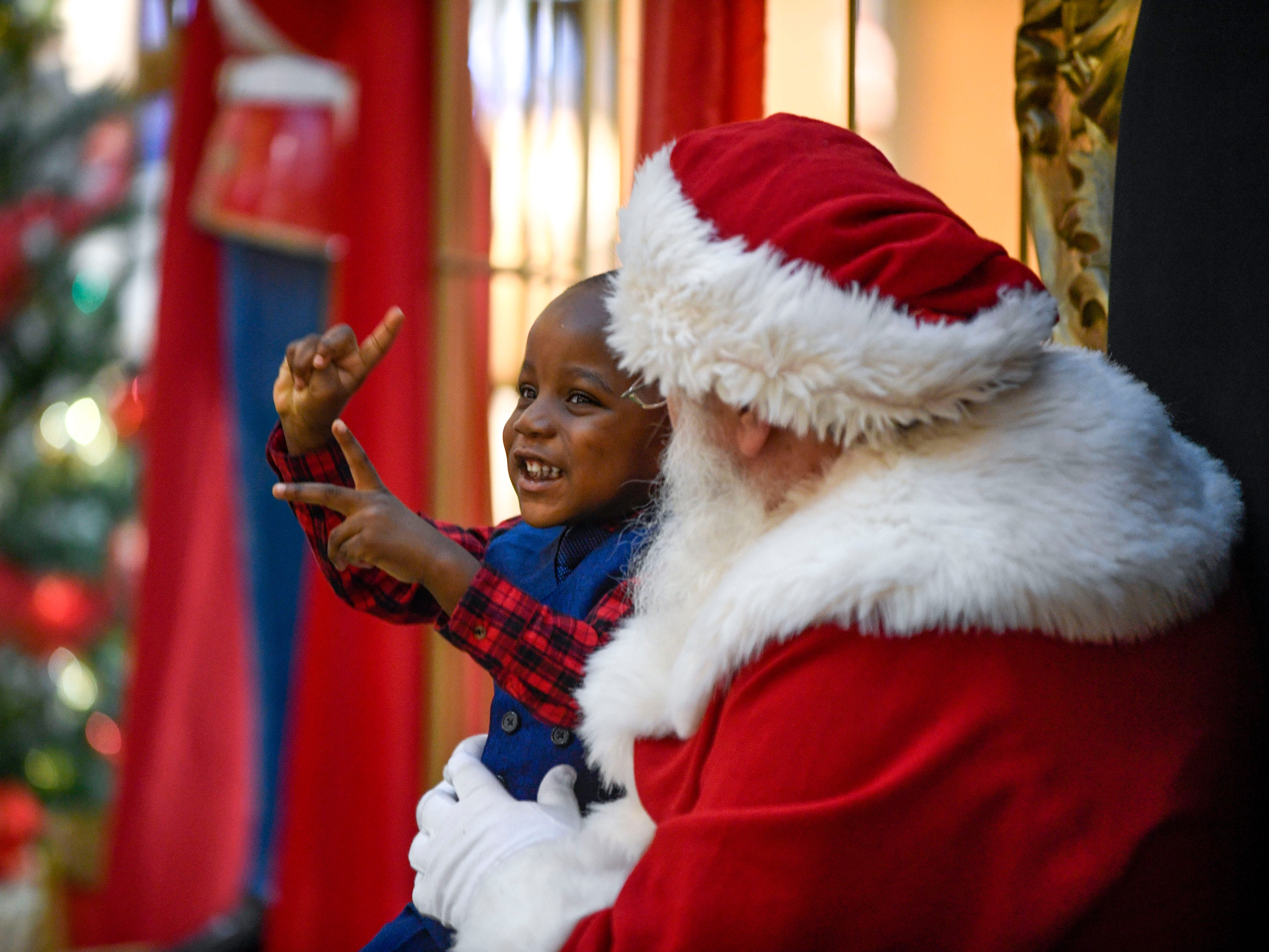 Ryan Lyonga, 2, waves his hands excitedly while being hoisted up for a photo with Santa Claus at Old Hickory Mall in Jackson, Tenn., on Wednesday, Nov. 21, 2018.