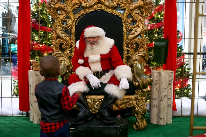 Santa Claus smiles down at Ryan Lyonga, 2, who just finished a successful picture taking session with Santa at Old Hickory Mall in Jackson, Tenn., on Wednesday, Nov. 21, 2018.
