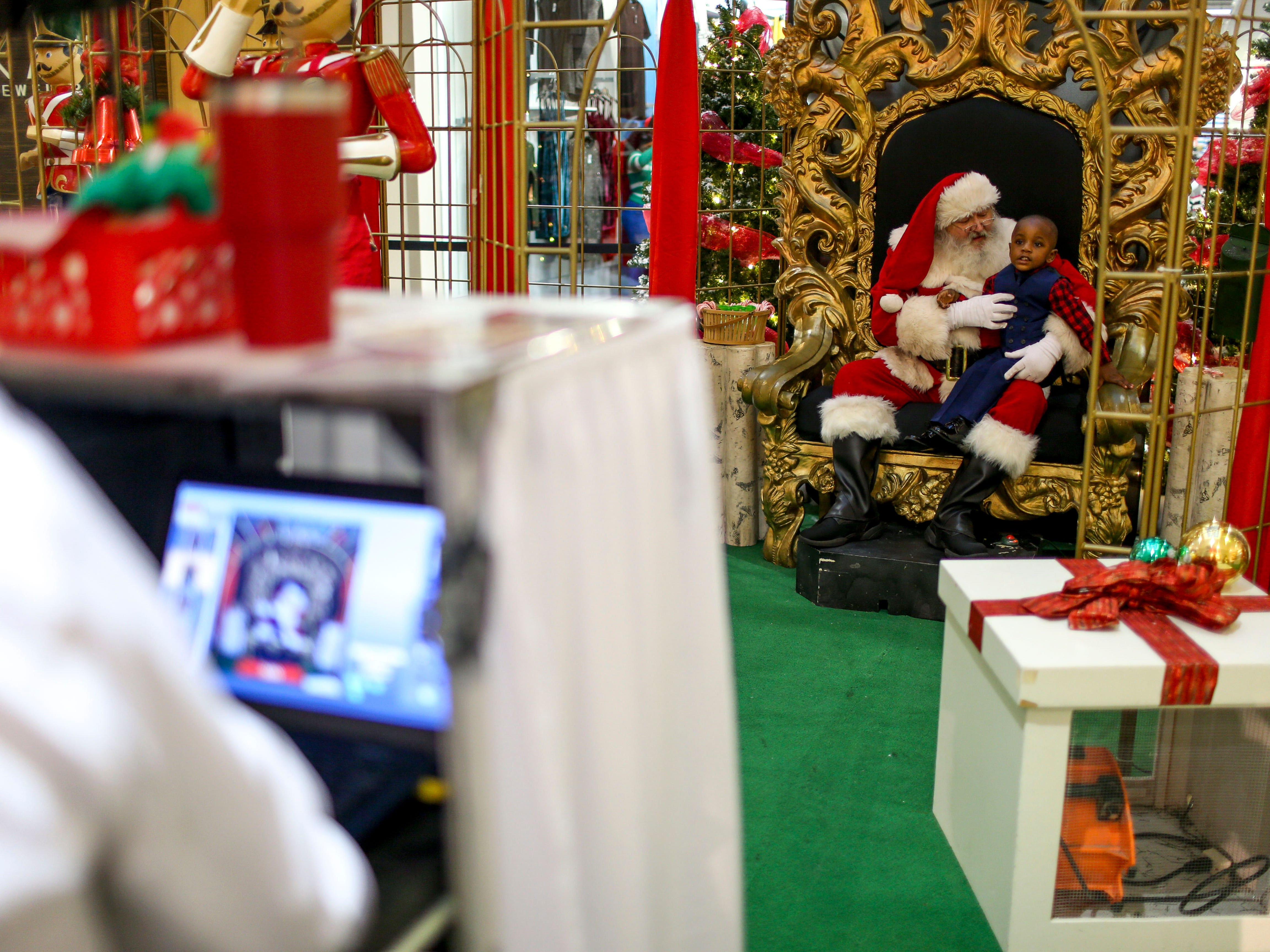 Cherry Hill employees operate a camera booth while Ryan Lyonga, 2, gets his photo taken with Santa Claus at Old Hickory Mall in Jackson, Tenn., on Wednesday, Nov. 21, 2018.