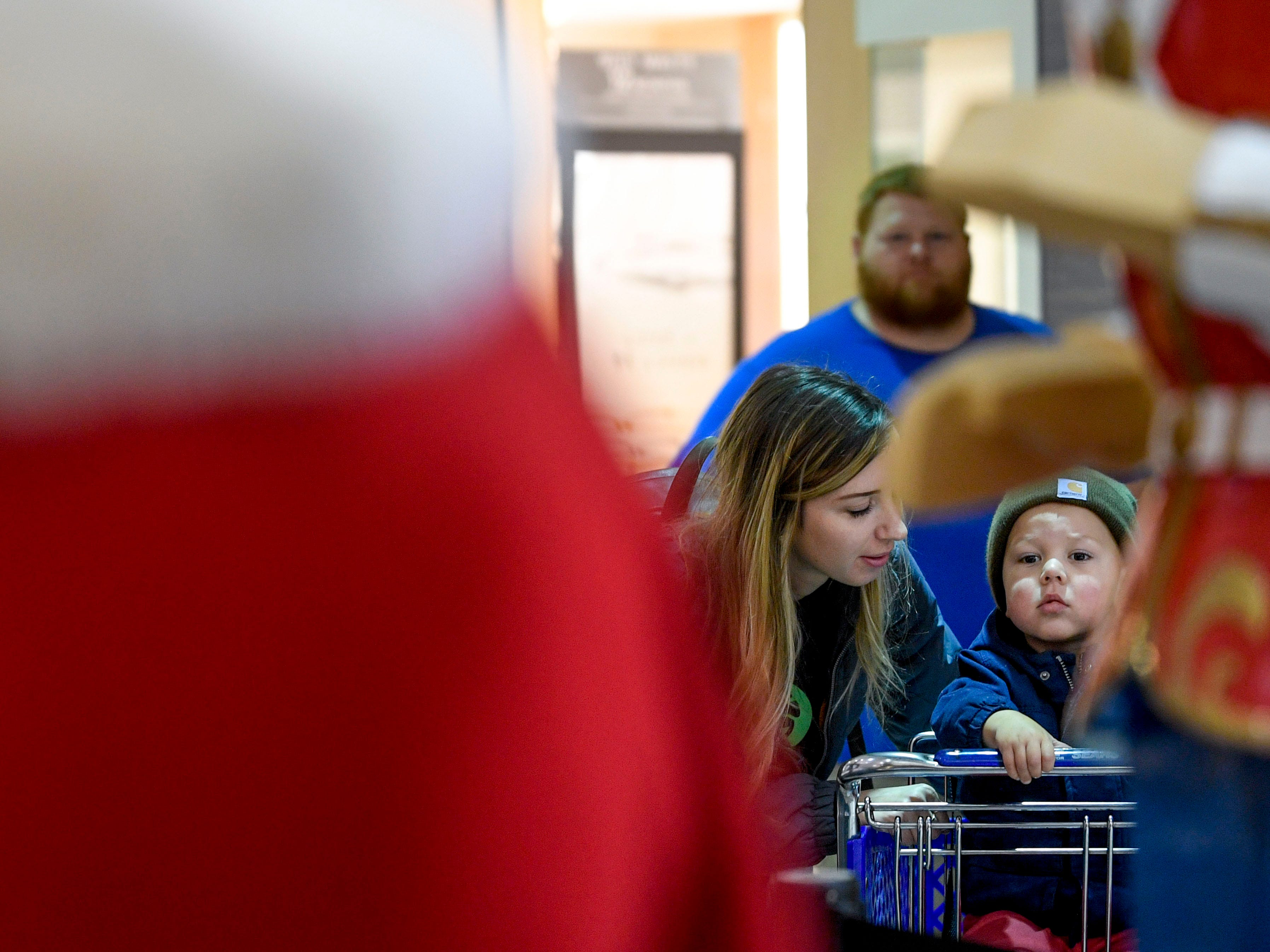 "Cause Gray whispers to her newly adopted son Grayson Gray, 3, that they have to go but will return to get photos taken with Santa Claus at Old Hickory Mall in Jackson, Tenn., on Wednesday, Nov. 21, 2018. ""We just got to adopt him this summer,"" Gray said. ""It'll be our first time, we're so excited."""