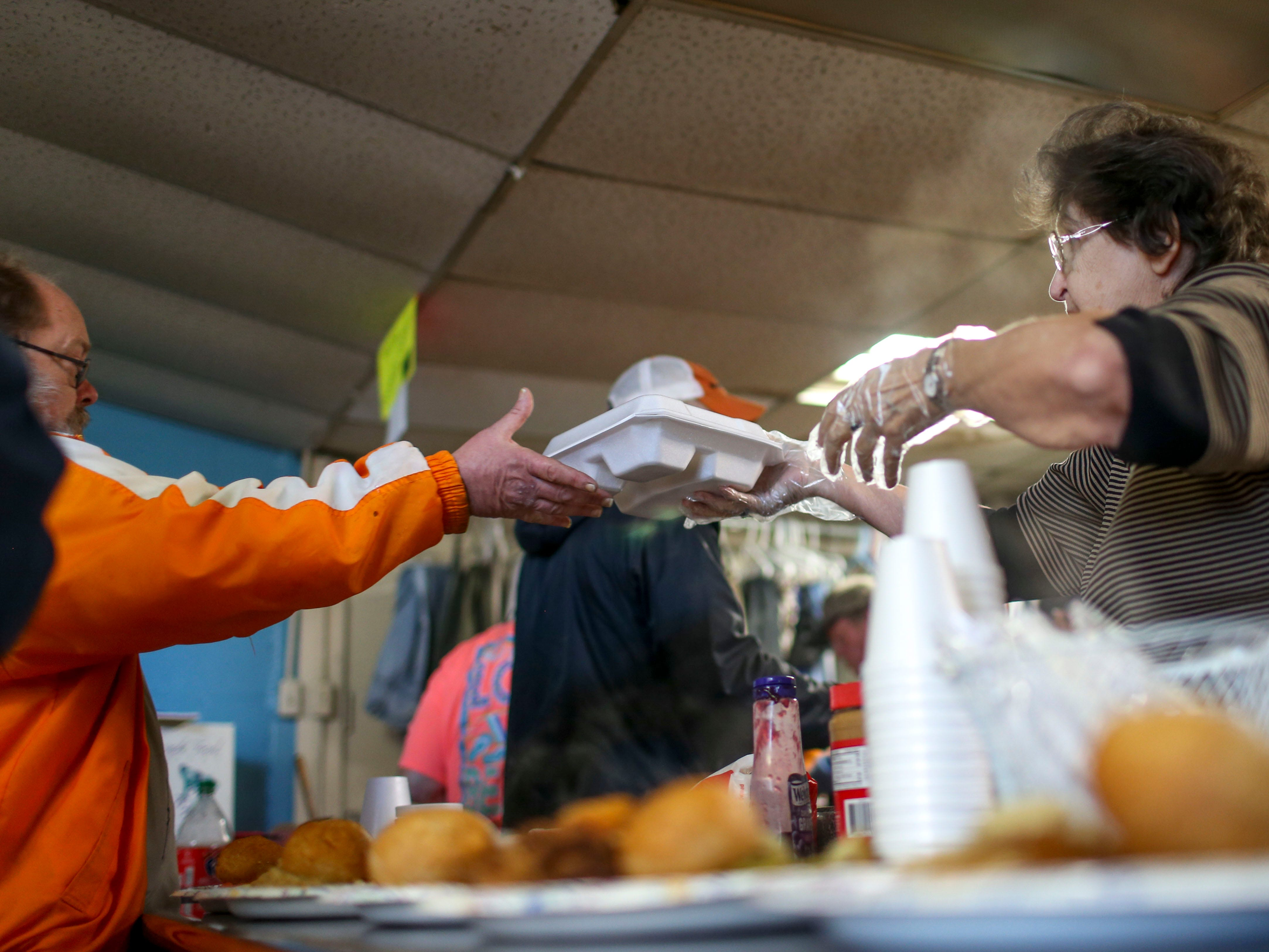 Judith Hindman passes a to-go plate to Greg Anderson to distribution amongst those arriving late and needing to head out the door at the annual Thanksgiving meal put on by Safe Harbor Day Mission in Jackson, Tenn., on Wednesday, Nov. 21, 2018.