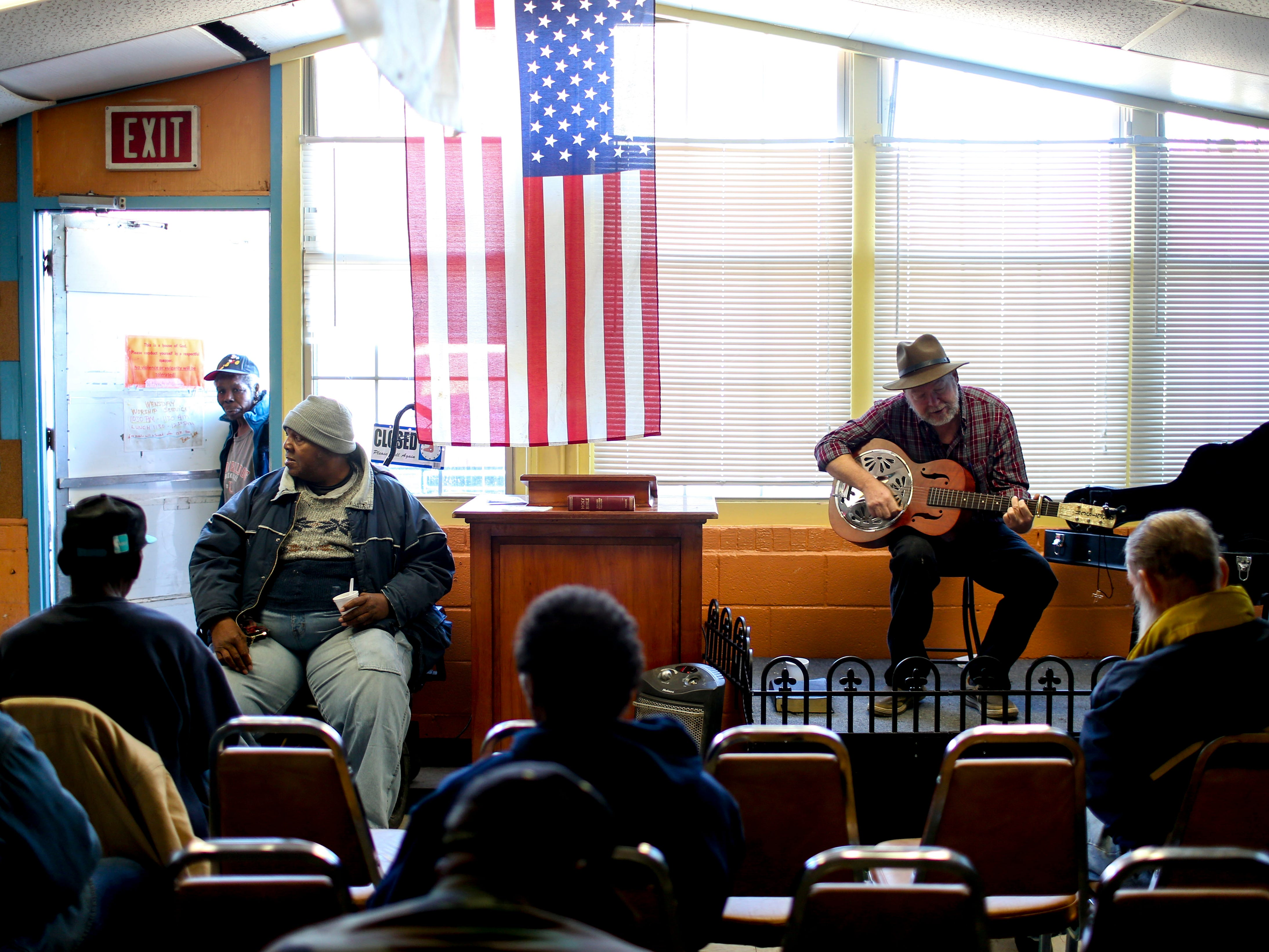 Lee Gaugh, right, sings and plays guitar at the annual Thanksgiving meal put on by Safe Harbor Day Mission in Jackson, Tenn., on Wednesday, Nov. 21, 2018.