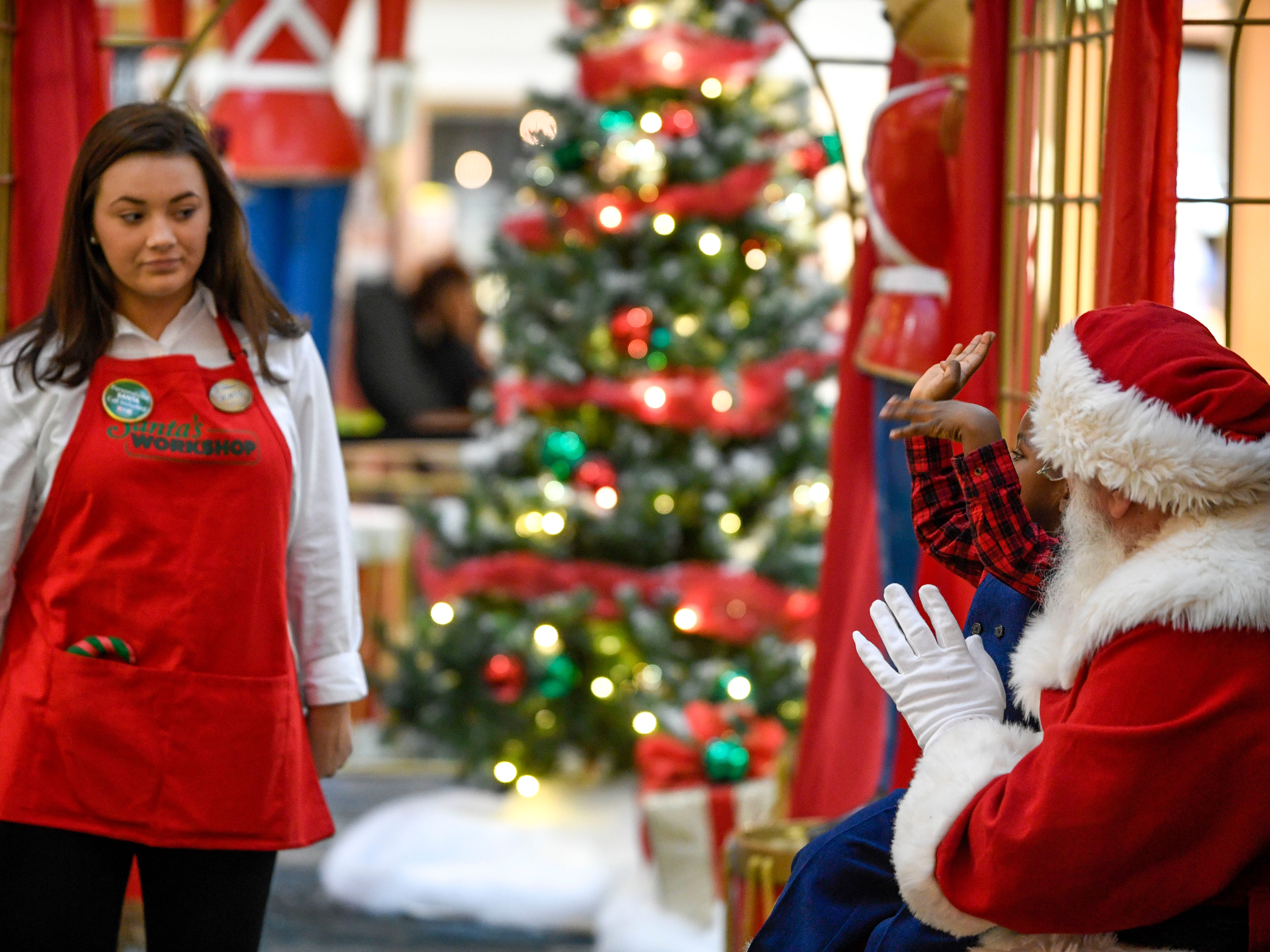 Kayla Grace Sharp, left, and Santa Claus try to distract Ryan Lyonga, 2, long enough to snap a photo with Santa at Old Hickory Mall in Jackson, Tenn., on Wednesday, Nov. 21, 2018.