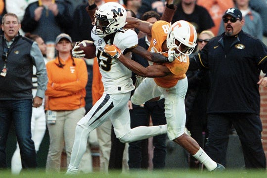 Tennessee defensive back Nigel Warrior (18) tries to tackle Missouri wide receiver Kam Scott (13) as he runs the ball down the sideline during Saturday's game at Neyland Stadium on Saturday, Nov. 17, 2018.