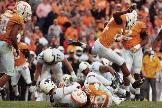 Tennessee defensive back Micah Abernathy (22) leaps over Missouri quarterback Drew Lock (3) and Tennessee defensive back Baylen Buchanan (28) during Saturday's game at Neyland Stadium on Saturday, Nov. 17, 2018.