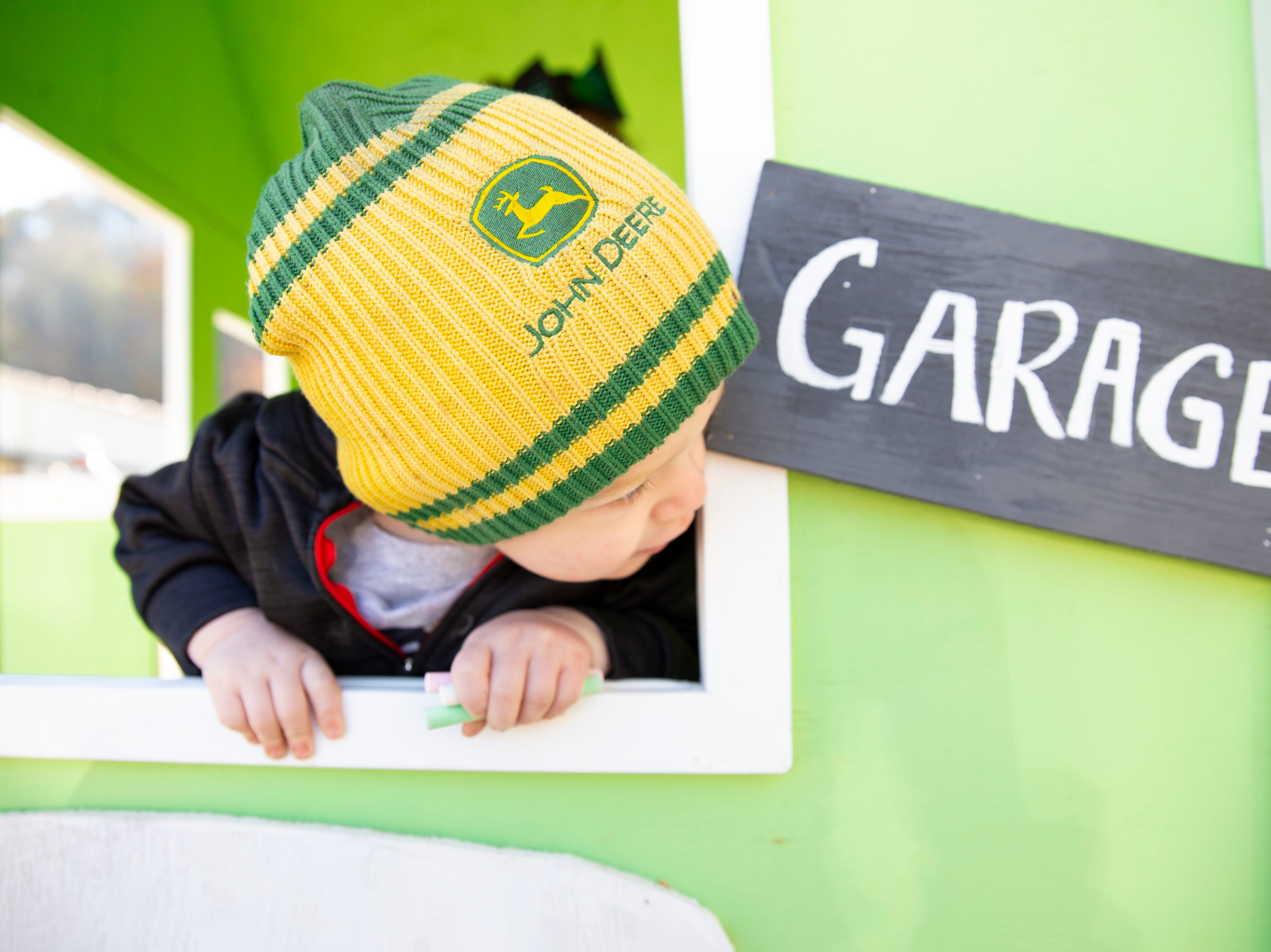 One-year-old Zayne Glenn peeks out of his new playhouse at TRU Homes in Halls.