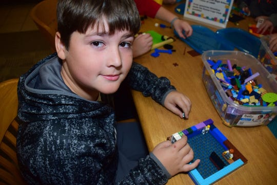 Aiden Durbin, 9, is well on the way with his build complete with people inside at the LEGO Club held at Karns Branch Library Saturday, Nov. 17.