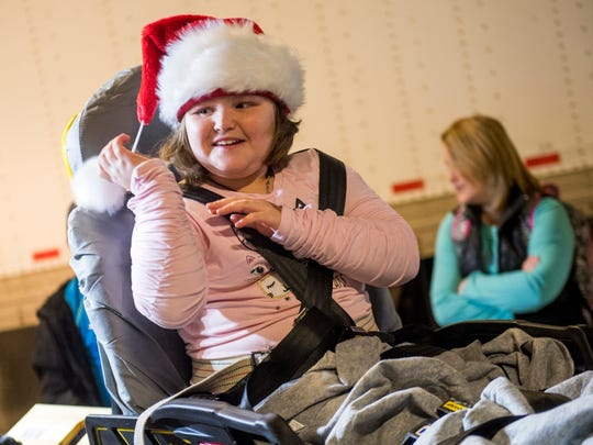 Ariel Epperson smiles after putting on a Santa Claus hat before entering the 34th annual Fantasy of Trees event held at the Knoxville Convention Center on Wednesday, November 21, 2018.