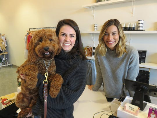 Owner Chelsea Brooks, center, with helper Kyla Martin and miniature goldendoodle, Chloe, are shown inside the Elyse Wilde store in Bearden on Nov. 19, 2018.