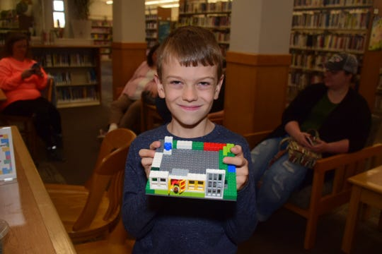 """Jeremiah Lowe, 7, shows off his build featuring a jail cell door at the LEGO Club held at Karns Branch Library Saturday, Nov. 17. He called it a """"window"""" house."""