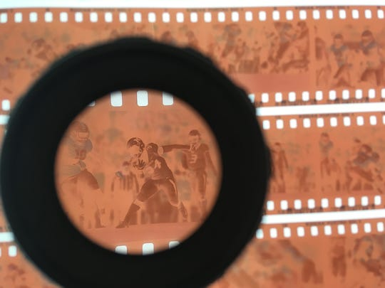 Looking through the film negatives on a light table with a loupe to find the selects to scan.