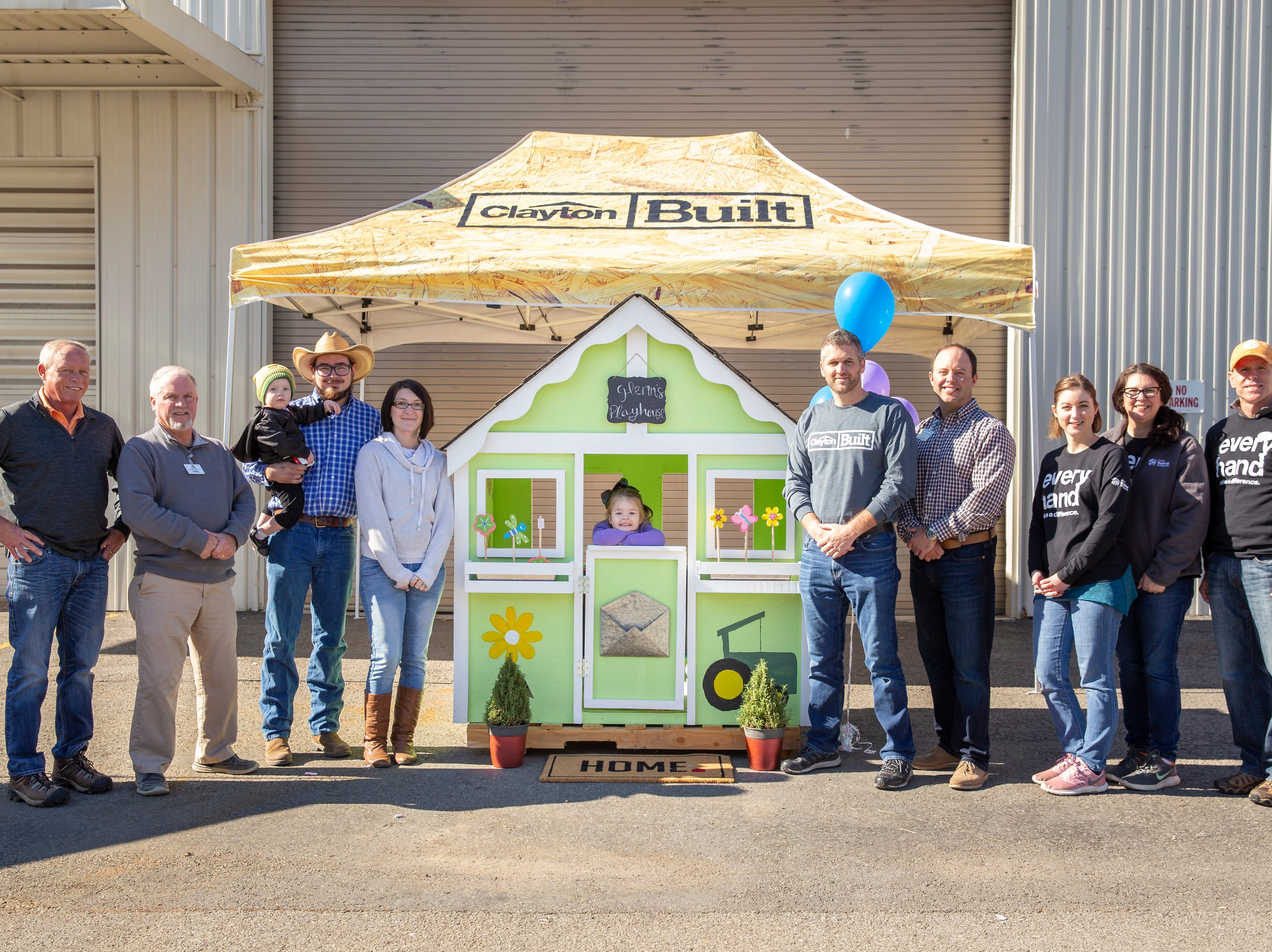 Michael and Amanda Glenn (center left), with their son, Zayne, and daughter, Sky, after they were presented with a playhouse at TRU Homes in Halls.