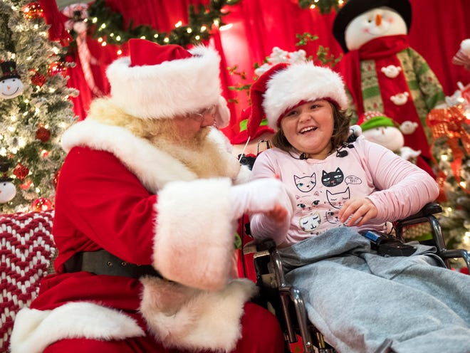 Ariel Epperson laughs as she shakes hands with Santa Claus during the 34th annual Fantasy of Trees event held at the Knoxville Convention Center on Wednesday, November 21, 2018.