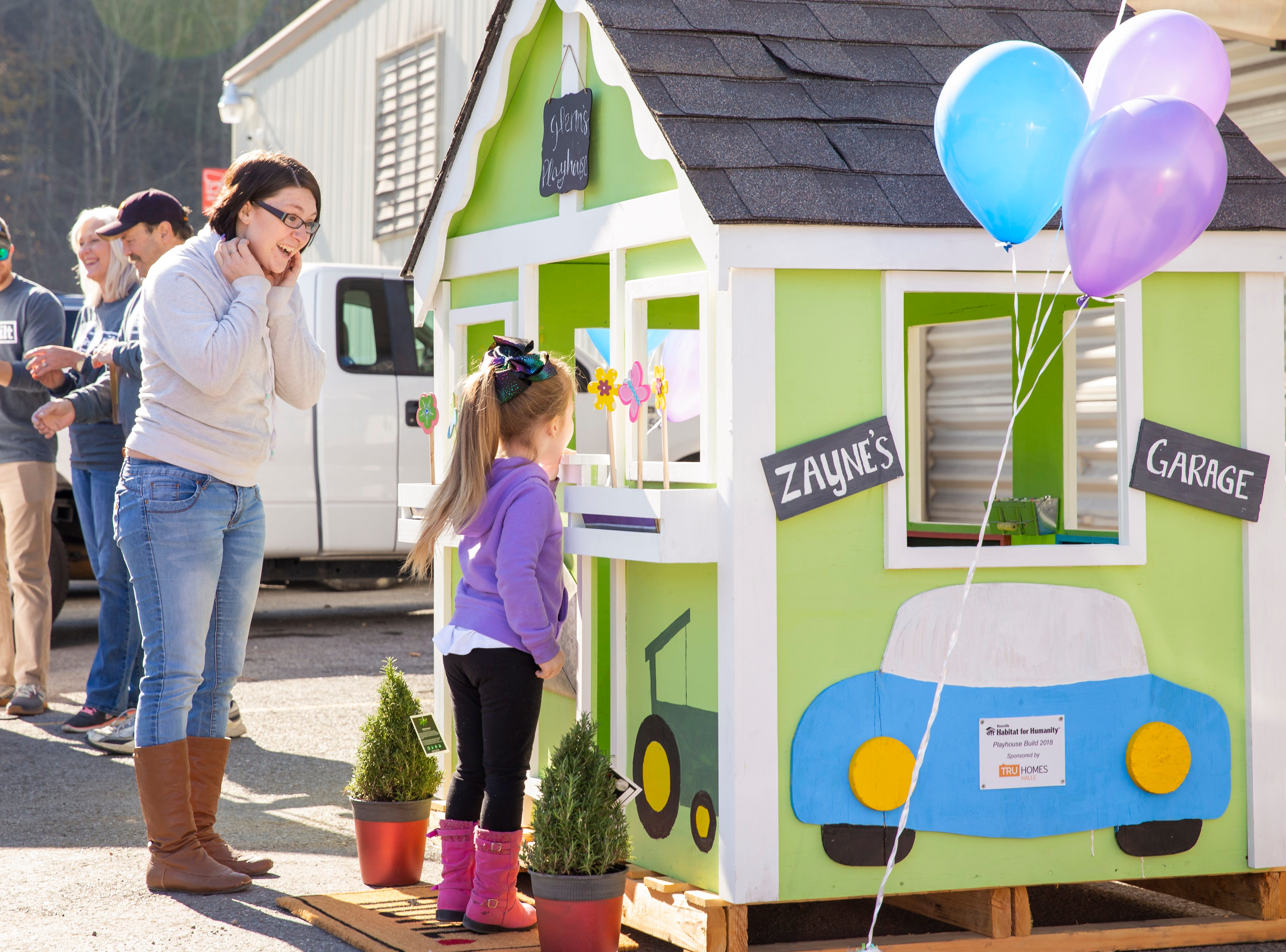 Amanda Glenn looks on as her 4-year-old daughter, Sky, peeks inside her new playhouse. TRU Homes Halls, a part of the Clayton Home Building Group, sponsored the Habitat for Humanity Project Playhouse. They painted and decorated the outside with some of the Glenn children's favorite things.