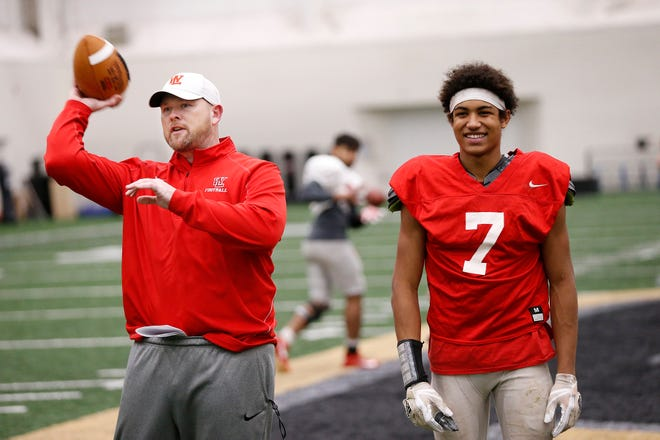 West Lafayette assistant coach Jon Speaker jokes with senior wide receiver Kyle Hazell as the Red Devils practice Tuesday inside the Mollenkopf Athletic Center on the campus of Purdue University.