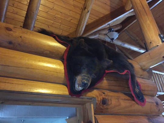 A bear skin rug hangs over the edge of a loft off the staircase inside a Hartland Township log cabin home, shown Wednesday, Nov. 21, 2018.
