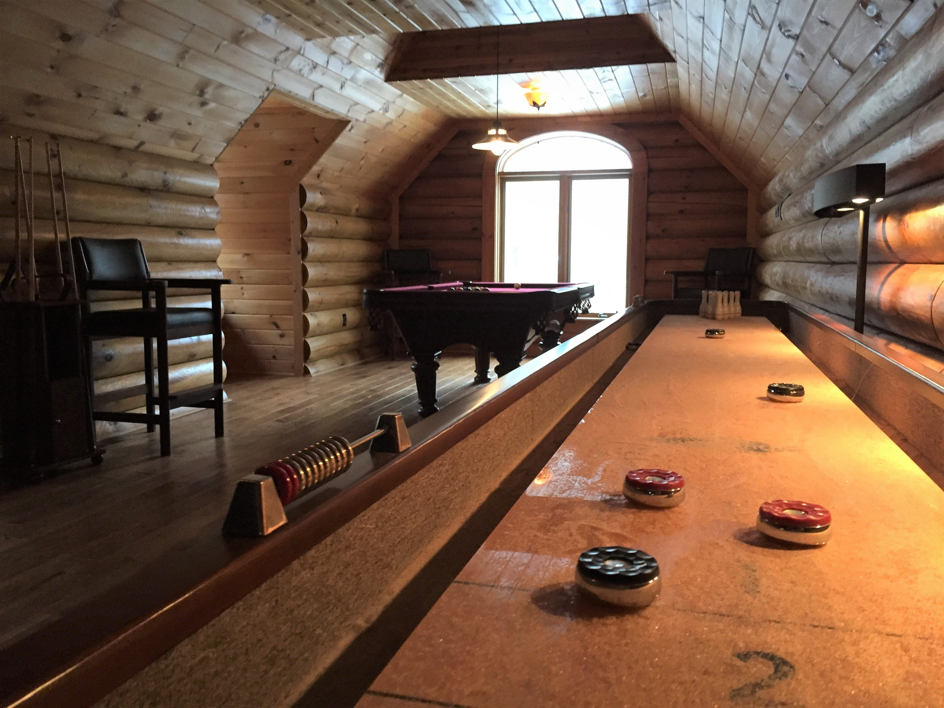 A pool table and shuffleboard are upstairs in a game room at a Hartland Township log cabin home, shown Wednesday, Nov. 21, 2018.