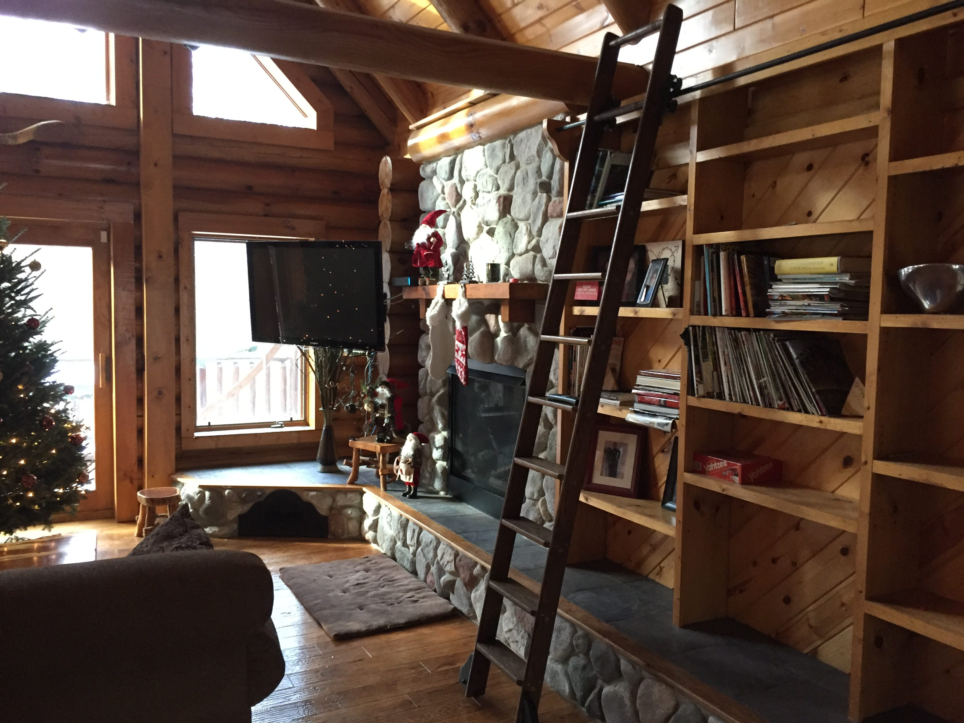 A bookshelf with a ladder and a see-through fireplace shared with the master bedroom are a few features of a log cabin home in Hartland Township, shown Wednesday, Nov. 21, 2018.
