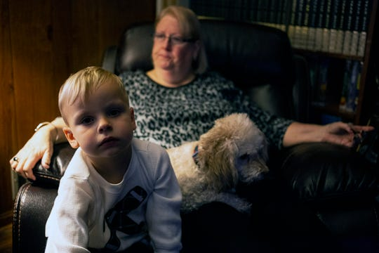 David William Saleh sits on the lap of Faye Saleh along with one of the family dogs Susie.