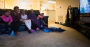 From left, the Goins twins and triplets, Devi, 5, Danijia, 13, Dimitria, 13, Divine, 13, and Demi, 5, watch television late Tuesday afternoon following school at their aunt's apartment in Lansing.