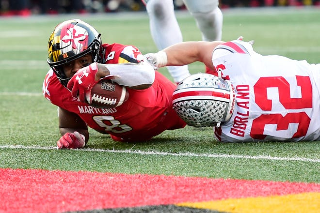 Maryland's Tayon Fleet-Davis dives past Ohio State linebacker Tuf Borland for a touchdown in overtime, but the 2-point conversion try failed as the Buckeyes held on a 52-51 victory last Saturday.