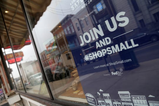 Signs promoting Small Business Saturday are posted around establishments participating in the event.