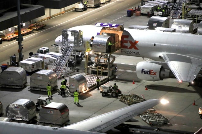 Shipping containers are unloaded from an aircraft at FedEx's Memphis superhub on Tuesday, November 20, 2018.