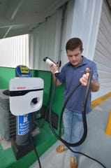 Sean Gorman and the charging device. Gorman's Auto Service on Marco Island has installed an electric vehicle charging station that is open to the public at their shop on East Elkcam Circle.