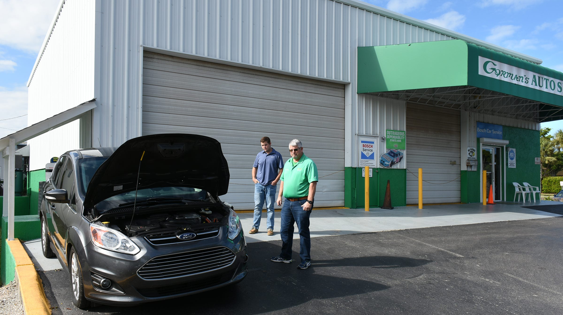 Father and son, Tim and Sean Gorman, watch as a vehicle charges at the charging station they installed Gorman's Auto Service on Marco Island.