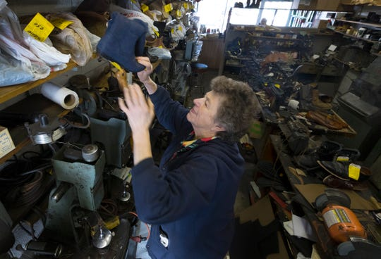Judy Gerasopoulos retrieves a pair of shoes for a customer at Cobbler Shoe Service. She and her husband, Pete, have run the business for decades, but they are retiring and closing up shop.