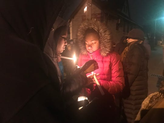 Cherise Dawson (left) lights candles with her 13-year-old daughter, Kendra Perkins, outside the home of Sandra Parks on Milwaukee's north side Tuesday evening. Dozens of people came to a vigil in honor of Sandra, who was shot to death Monday night while she was in her bedroom.