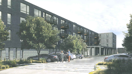This architectural rendering shows the rear parking lot of the 48-unit apartment building proposed at the former Prange Greenhouse site, at 2510 W. Good Hope Road. The development also includes 41 three-bedroom townhomes on the north end of the property.