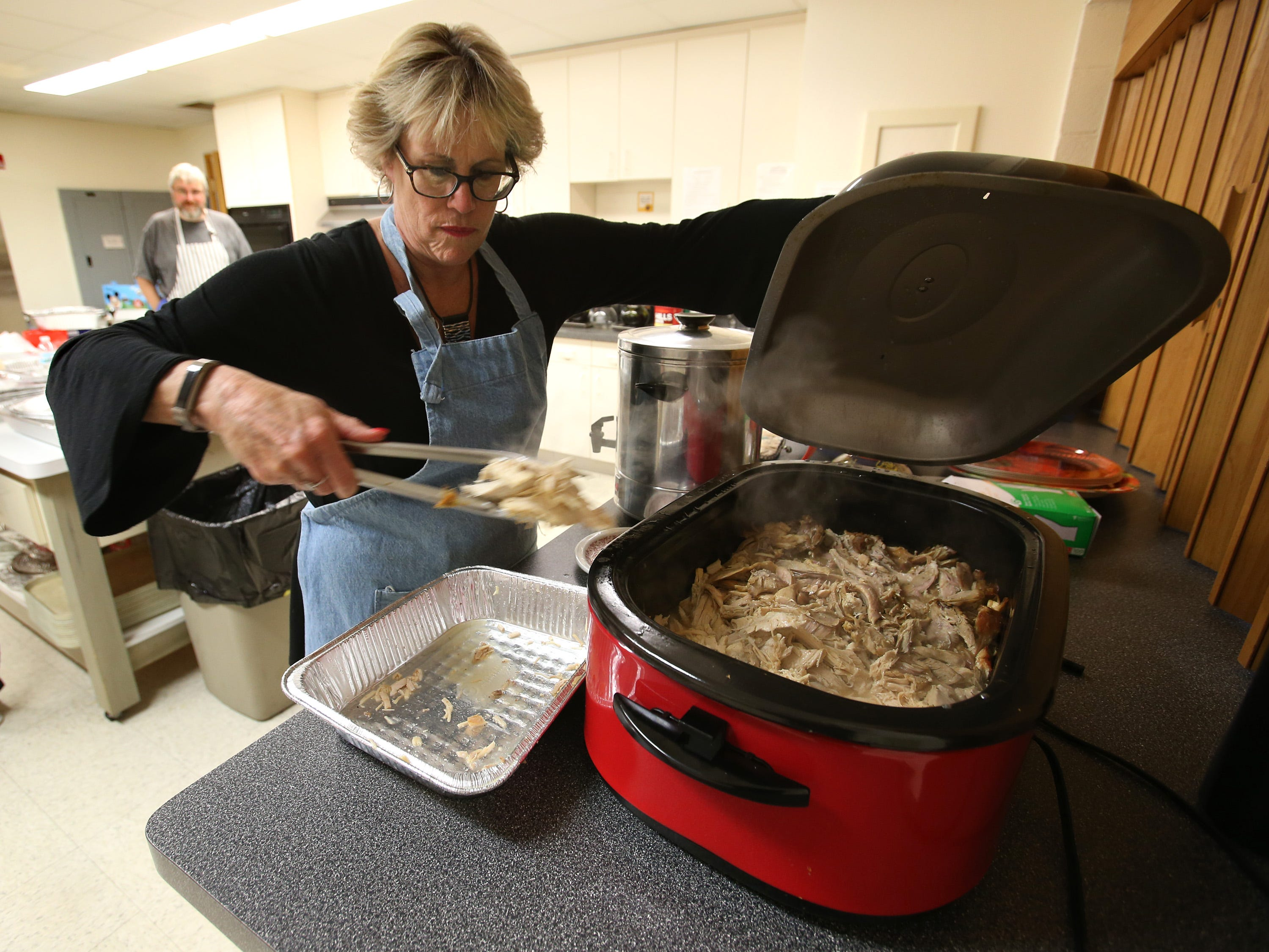 Pam Behrend transfers turkey into a chaffing dish pan for serving to an anticipated 400 diners at the Christ the King Lutheran Church's seventh annual Thanksgiving Gathering on Nov. 21.