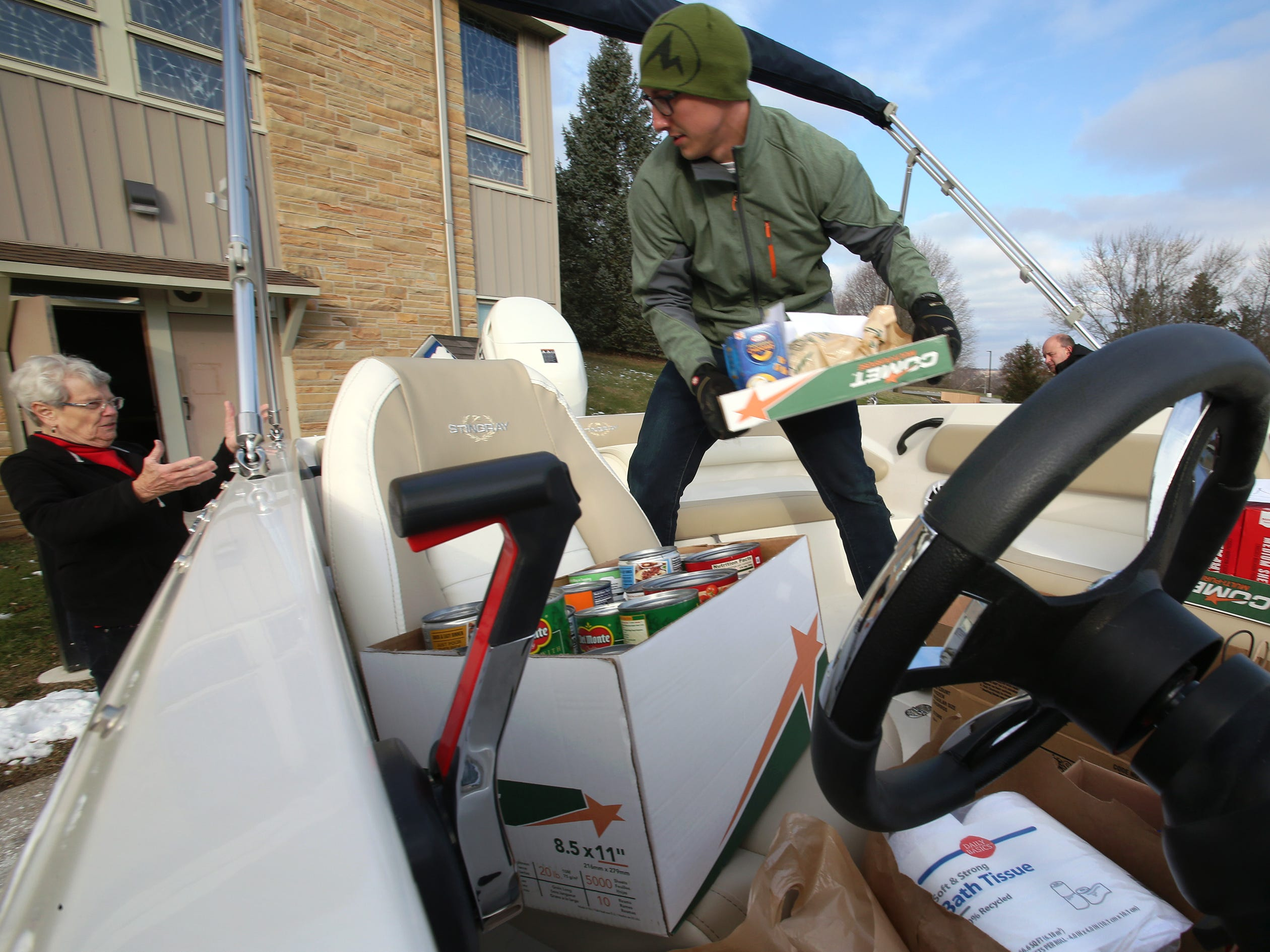 Mitchel Griep of CenterPointe Boat Services hands off a flat of foodstuffs to Karen Semrad from a boat used to transport a major food donation to the Pewaukee Food Pantry at Gethsemane United Methodist Church on Nov. 21. CenterPointe collected donations from customers and transported a collection by Pewaukee's Asa Clark Middle School that the students had presorted by type and date.