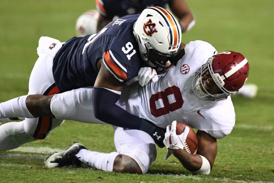 Alabama running back Josh Jacobs (8) is brought down by Auburn defensive lineman Nick Coe (91) during the Iron Bowl on Nov. 25, 2017, in Auburn, Ala.