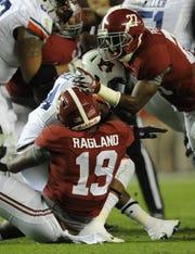 Alabama linebacker Reggie Ragland (19) and Alabama defensive back Nick Perry (27) stop Auburn quarterback Nick Marshall in the Iron Bowl at Bryant-Denny Stadium in Tuscaloosa, Ala. on Saturday November 29, 2014.