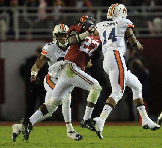 Auburn quarterback Nick Marshall (14) stiff arms Alabama defensive back Nick Perry in the Iron Bowl at Bryant-Denny Stadium in Tuscaloosa, Ala. on Saturday November 29, 2014.
