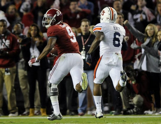 Alabama wide receiver Amari Cooper (9) heads to the end zone on a 75 yard touchdown against Auburn defensive back Jonathon Mincy (6) the Iron Bowl at Bryant-Denny Stadium in Tuscaloosa, Ala. on Saturday November 29, 2014.