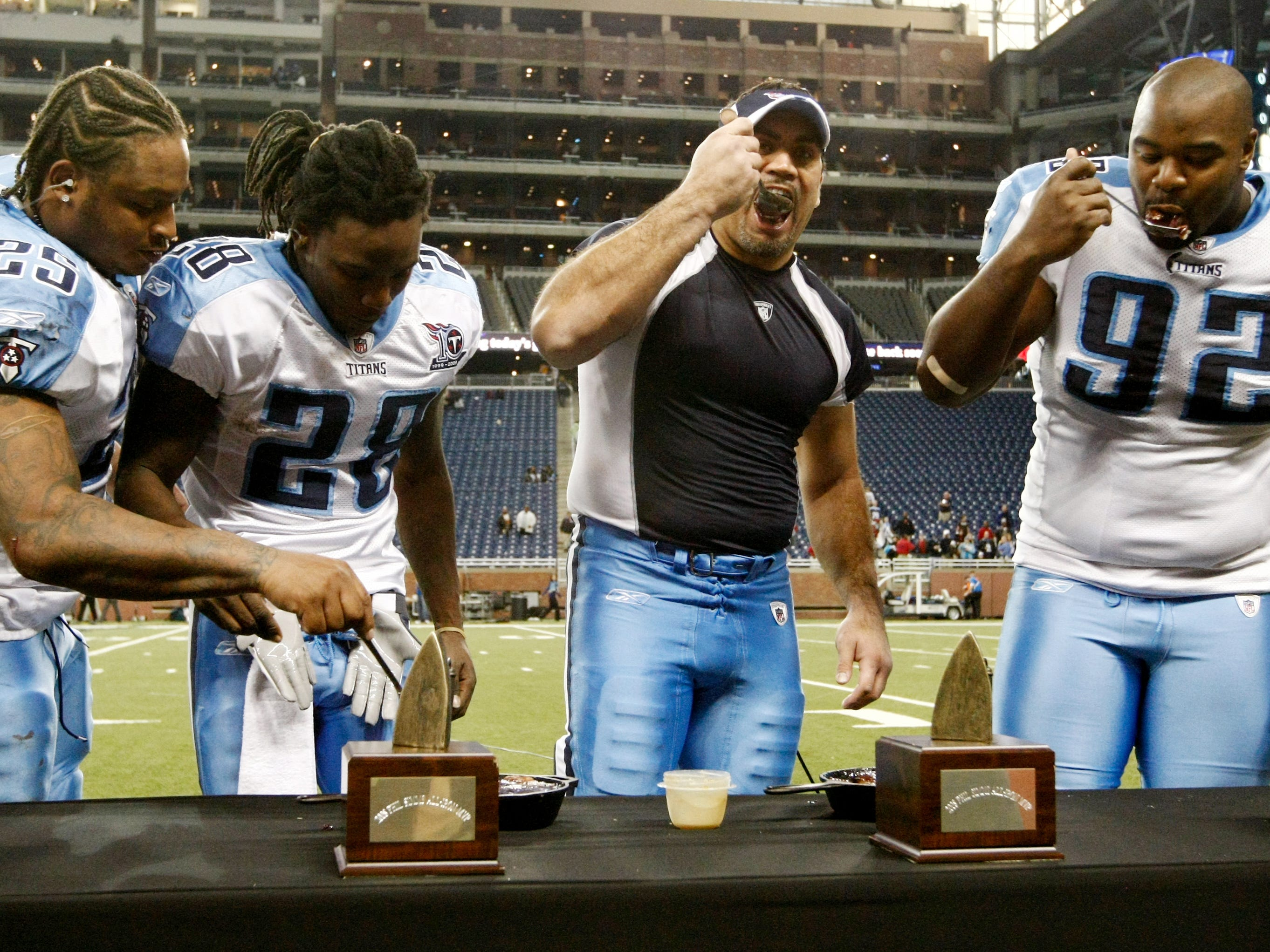 "Tennessee Titans running back LenDale White (25), running back Chris Johnson (28), center Kevin Mawae and defensive tackle Albert Haynesworth (92) enjoy a pie and receive their ""iron man"" award for defeating the Detroit Lions 47-10 on Thanksgiving Day Nov. 25, 2008 at Ford Field in Detroit."